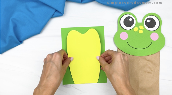 hand gluing belly to paper bag frog body