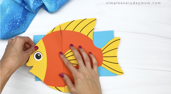 hand gluing head to paper bag fish craft