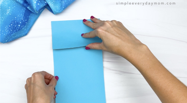 hand gluing blue paper to brown paper bag