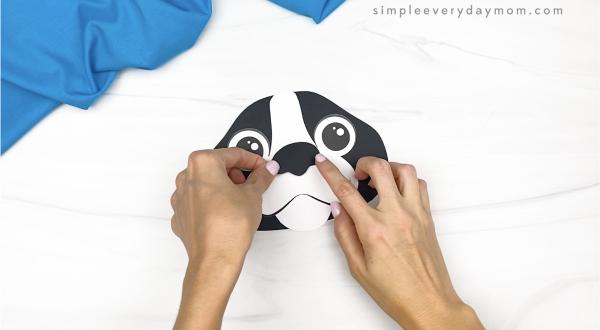 hand gluing nose to paper bag dog craft