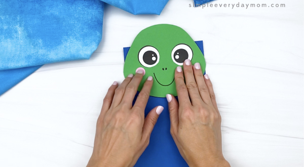 hand gluing head to paper bag turtle craft