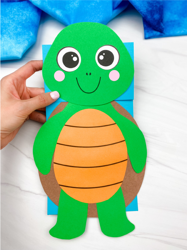 hand holding paper bag turtle craft