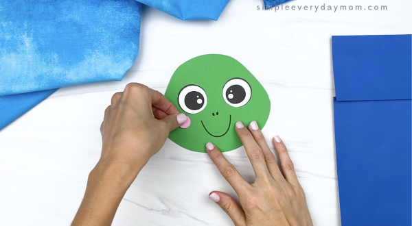 hand gluing cheek to paper bag turtle head