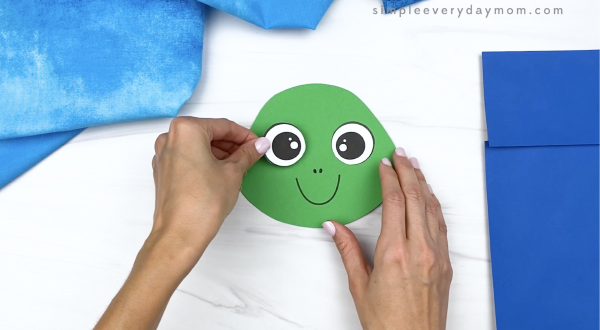 hand gluing eye to paper bag turtle head