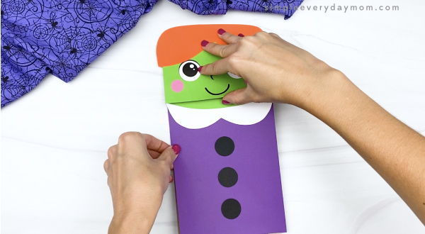 hand gluing dress to paper bag witch craft