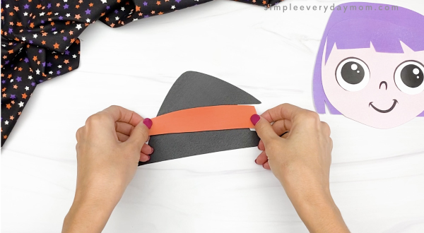 hand gluing hat band to printable witch craft