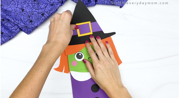 hand gluing hat to paper bag witch craft