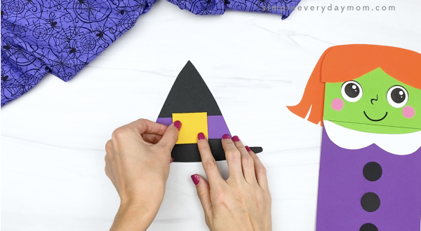 hand gluing outer buckle to paper bag witch hat