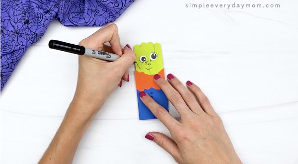 hand drawing stitches onto zombie popsicle stick craft