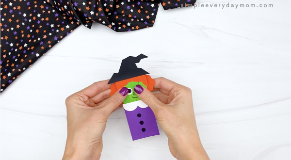 hand gluing back of hair to popsicle stick witch craft