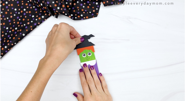 hand gluing hat to popsicle stick witch craft