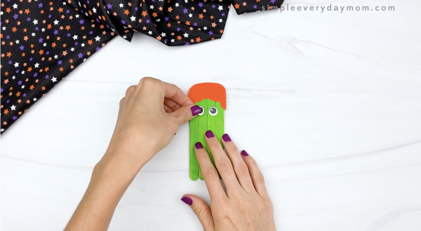 hand gluing eye to popsicle stick witch craft