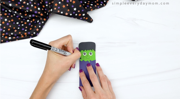 hand drawing stitches onto popsicle stick Frankenstein craft