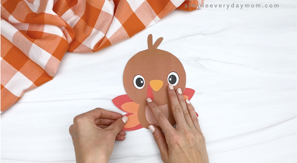 hand gluing feathers to turkey printable craft