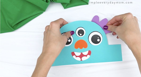 hand gluing ears to monster headband craft