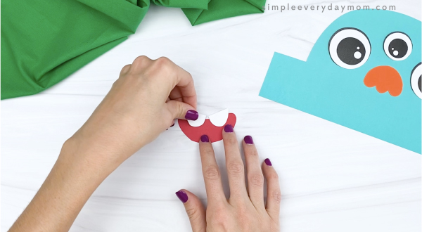 hand gluing teeth to mouth of monster headband craft