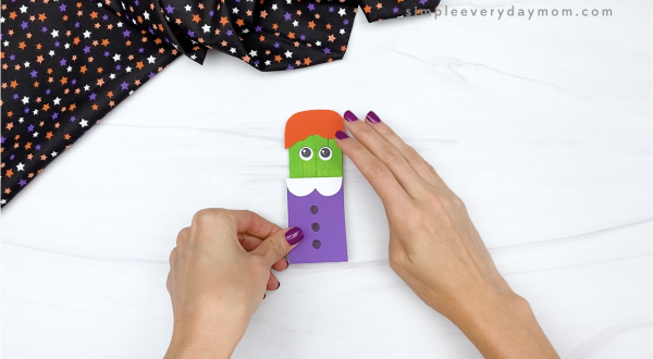 hand gluing dress to popsicle stick witch craft