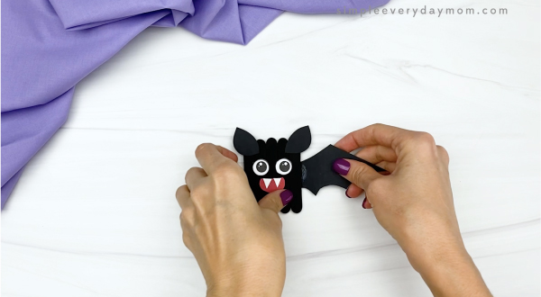 hand gluing wing to popsicle stick bat craft