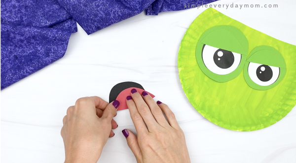 hand gluing tongue to mouth of paper plate zombie craft