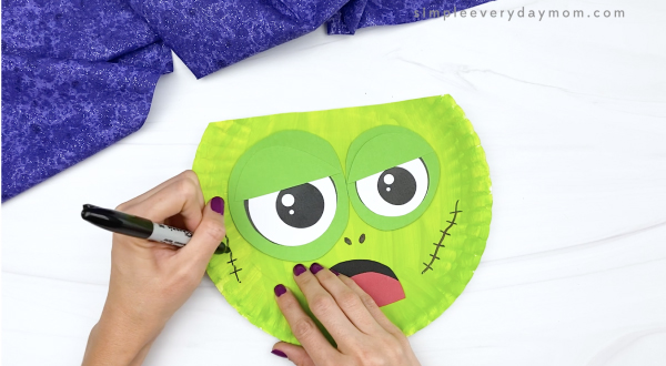 hand drawing stitches onto paper plate zombie craft