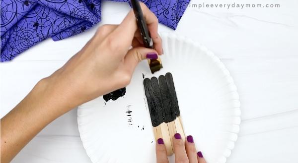 hand painting popsicle sticks black