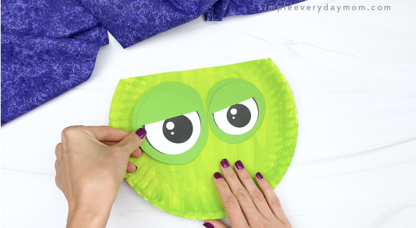 hand gluing eyes to zombie paper plate craft