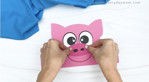 hand gluing nose to pig headband craft