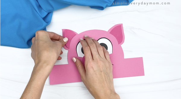hand gluing inner ear to pig headband craft