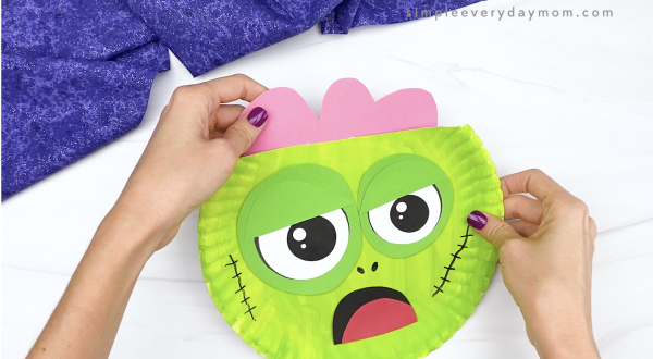 hand gluing brain to top of zombie paper plate craft