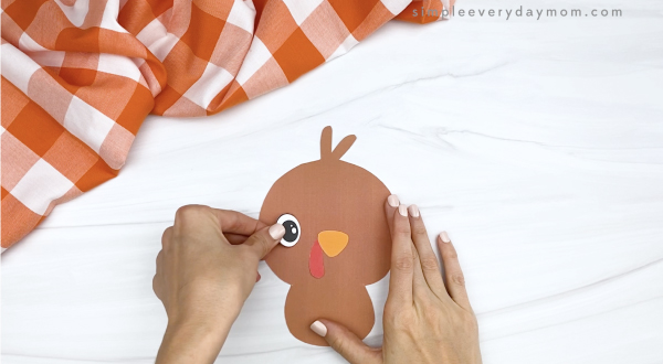 hand gluing eyes to turkey printable craft