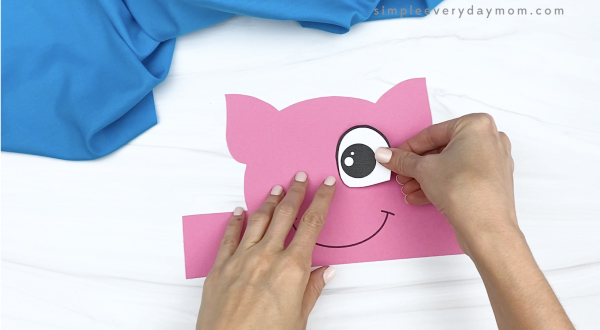hand gluing eyes to pig headband craft