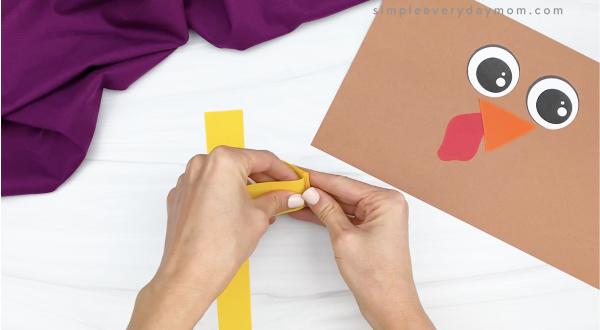 hand folding yellow paper to create turkey legs