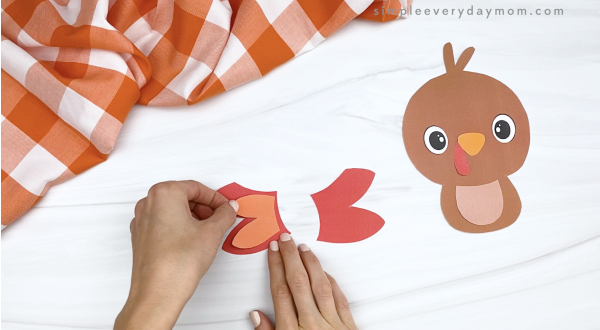 hand gluing inner feather to outer feathers of printable turkey craft