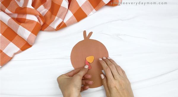 hand gluing beak and snood to turkey printable craft