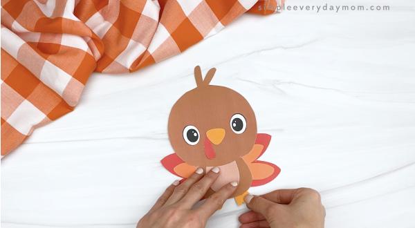 hand gluing feet to turkey printable craft