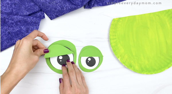 hand gluing eyelid to eyes of paper plate zombie craft