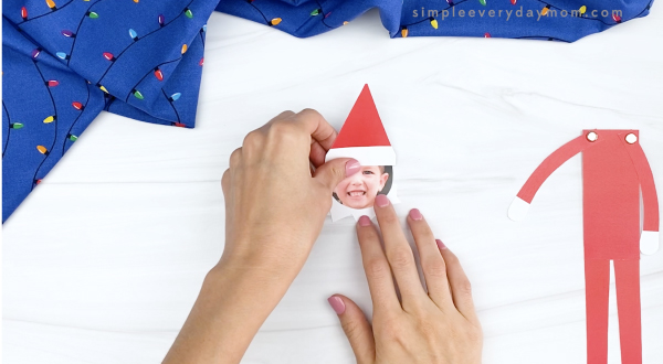 hand gluing head to collar of elf on the shelf craft