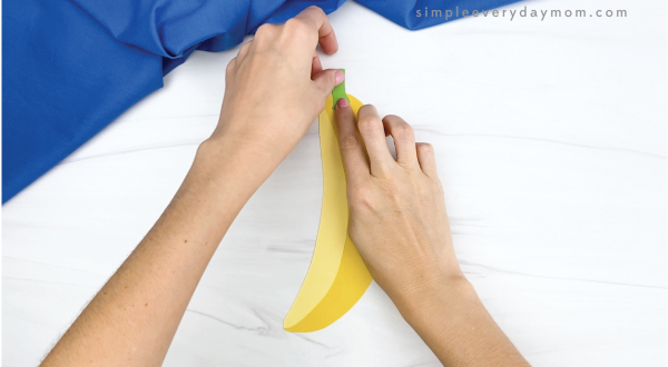 hand gluing stem onto paper banana craft
