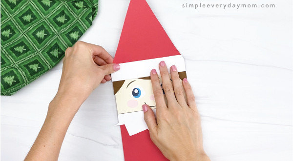 hand gluing hat to elf on the the shelf puppet craft