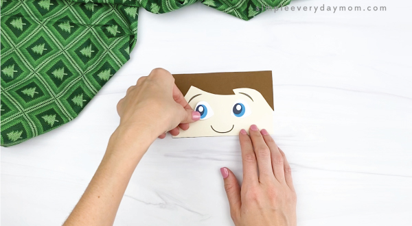 hand gluing eye to elf on the the shelf puppet craft