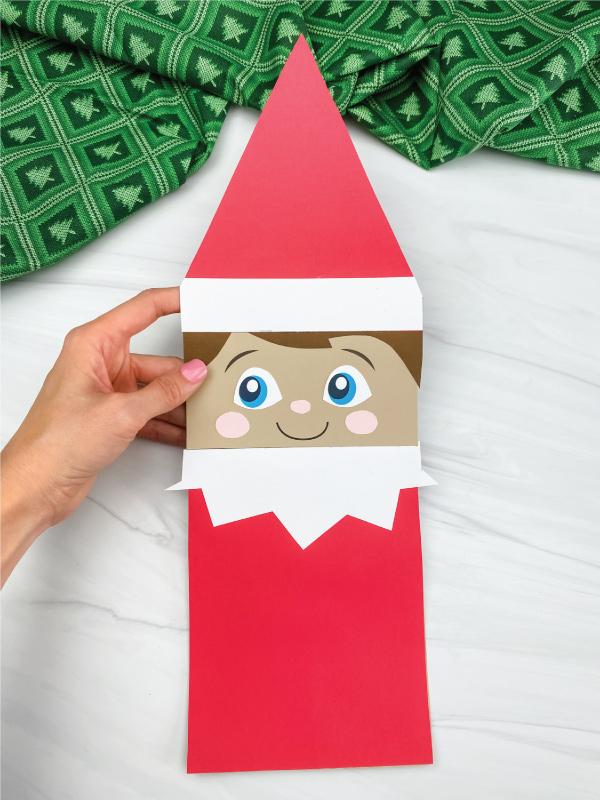 hand holding elf on the shelf paper bag craft