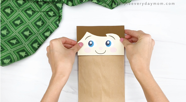hand gluing head to elf on the the shelf puppet craft