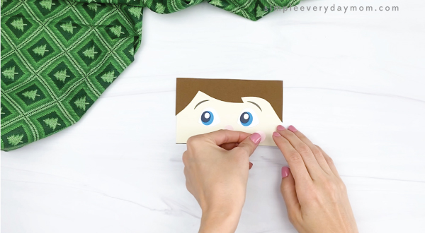 hand gluing cheek to elf on the the shelf puppet craft